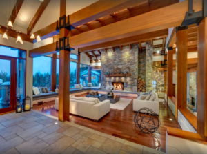 Photo of the Belmont Estate great room, with wooden beams, couches, fireplace with stone accents and a view outside of the snow in the evening.